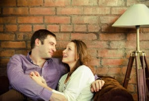 Happy couple talking and sitting on sofa